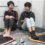 Photograph of the magical musical mat. two women sit on floor surrounded by four mats. each woman has their feet resting a different mat and they are not wearing shoes. mats shape (hexagon, heart, circle, triangle) color (green, pink, blue, orange).